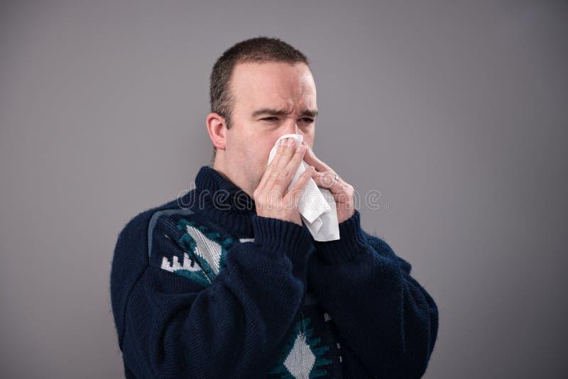 Man som blåser hans näsa som skjutas på grå färger arkivbilder