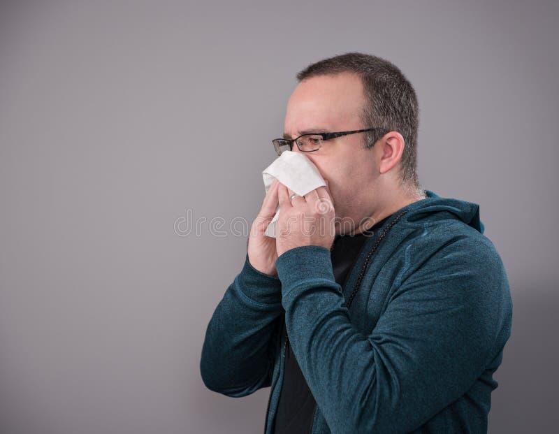 Man som blåser näsan som skjutas på grå färger arkivfoto