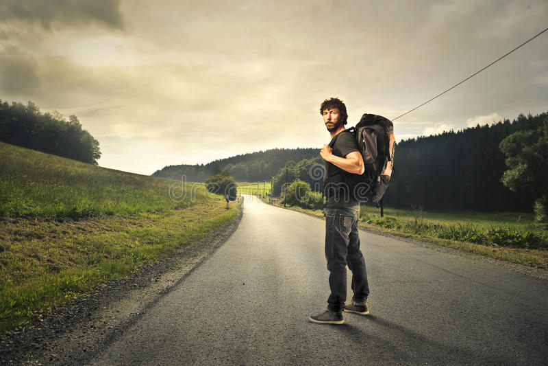 Man som bort går med en ryggsäck arkivbilder