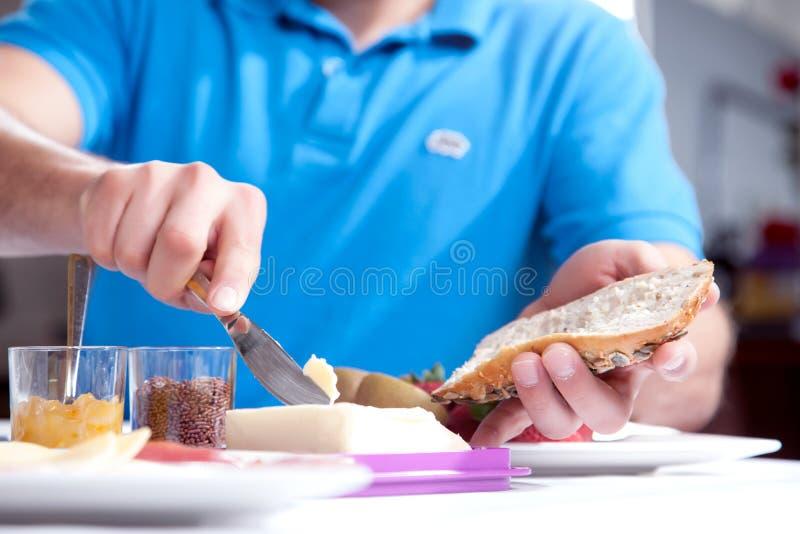 Man som breder smör på en skiva av wholewheatbröd royaltyfri foto