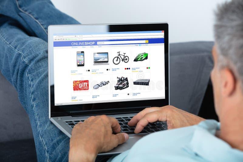 Man som direktanslutet shoppar p? b?rbara datorn arkivfoton