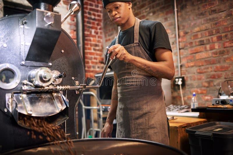 Man som drar spaken för att hälla våra kaffebönor från kaffebrännaren royaltyfri foto