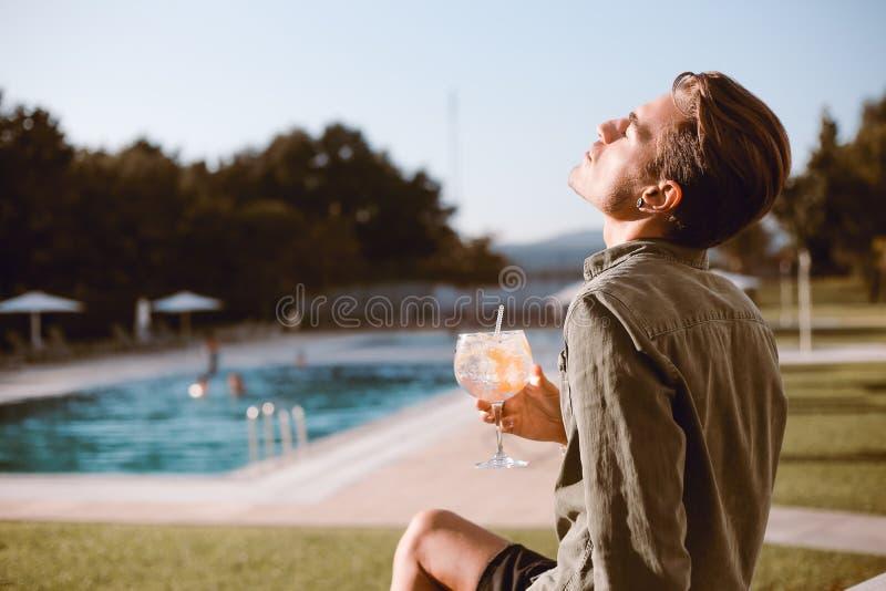 Man som dricker coctailen nära pölen arkivfoto