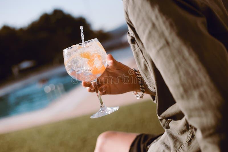 Man som dricker coctailen nära pölen royaltyfria foton