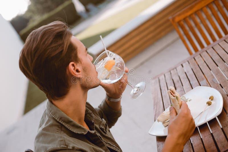 Man som dricker coctailen och att äta lunch royaltyfri bild