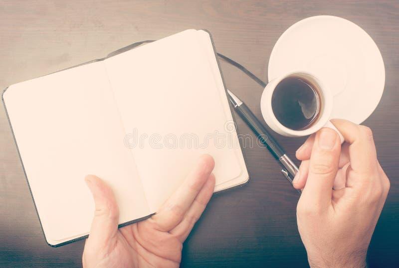 Man som dricker kaffe och kontrollerar hans anteckningsbok royaltyfri bild