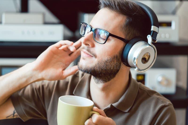 Man som dricker kaffe och lyssnar till musik royaltyfri fotografi