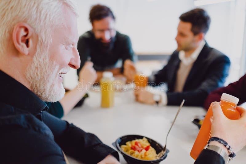 Man som dricker organisk fruktsaft i kafeterian och le för kontor royaltyfri fotografi