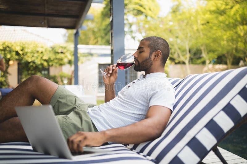 Man som dricker rött vin, medan koppla av på farstubron arkivfoto