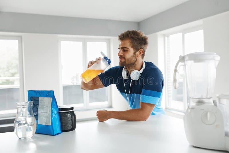 Man som dricker sportdrinken, innan utbildning Näringtillägg royaltyfria foton