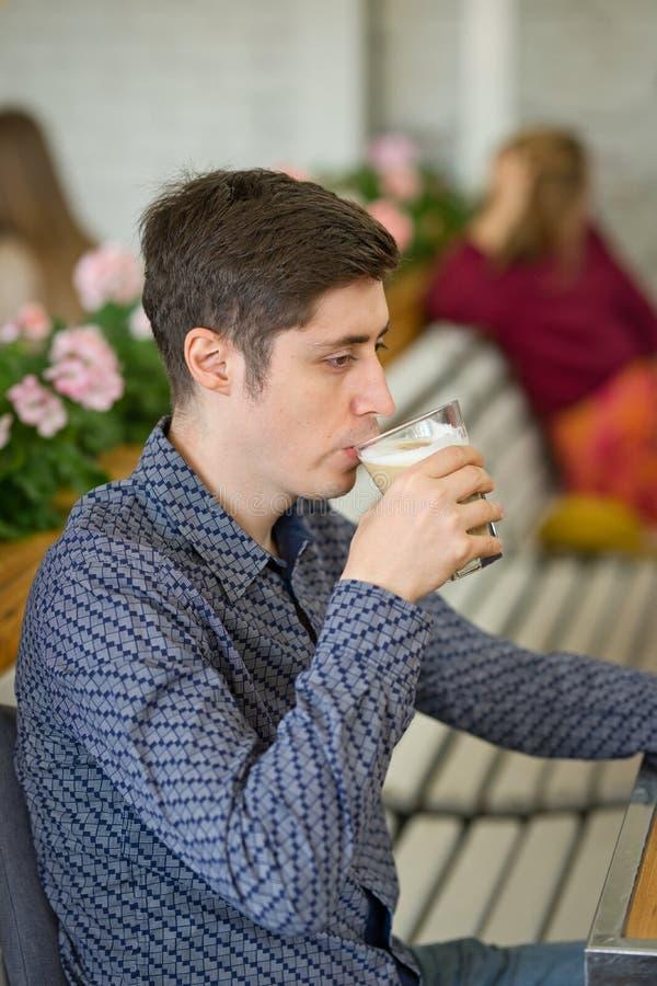 Man som dricker stor latte på en kafétabell arkivbilder