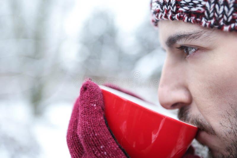 Man som dricker varmt te i vinter royaltyfria foton