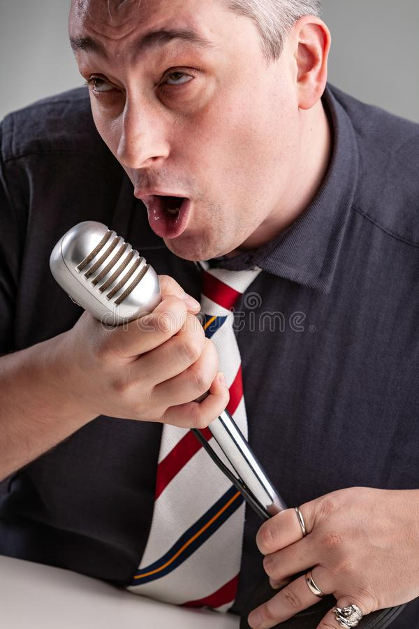 Man som fängslas i hans musik som rymmer en mikrofon royaltyfri fotografi