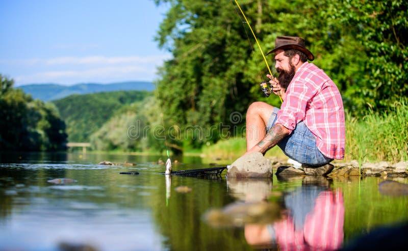 Man som fångar fisk Människan vid flodstränderna lever i ett fredligt idylliskt landskap när han fiskar Guy fly Flygningen lyckad royaltyfria bilder