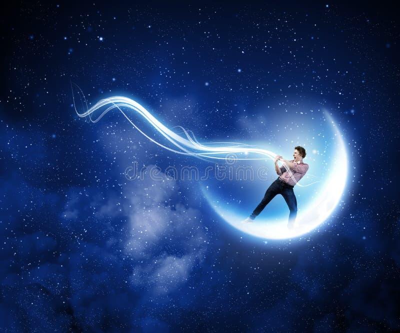 Man som fångar månen royaltyfri fotografi