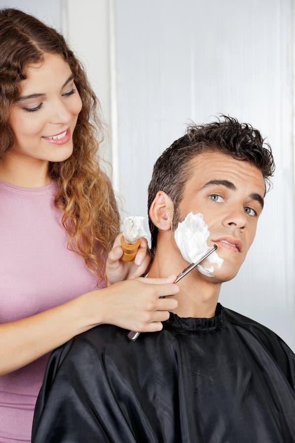 Man som får en rakning från kvinnlig barberare royaltyfria bilder