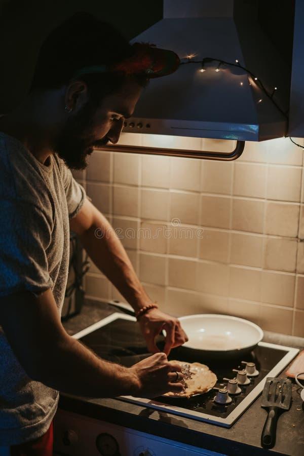 Man som förbereder pannkakor i köket på helgdagsafton för nya år royaltyfria bilder