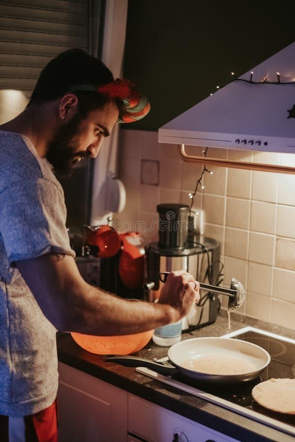 Man som förbereder pannkakor i köket på julhelgdagsafton royaltyfri fotografi