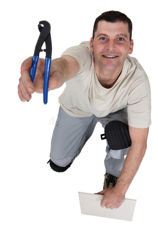 Man som förbereder sig att klippa tegelplattan royaltyfri bild