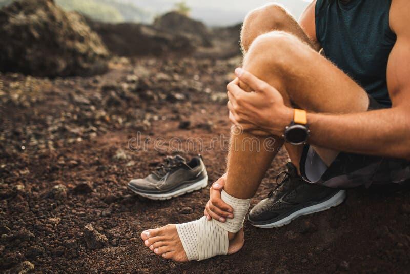 Man som förbinder den sårade ankeln Första hjälpen för ben arkivbilder