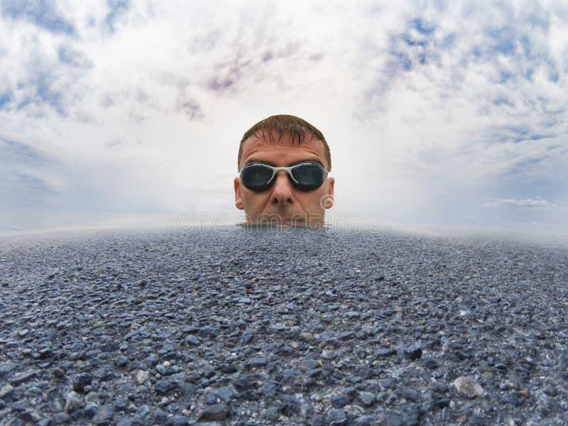 Man som fördjupas i mitt av ett hav av den asfaltvatten och clouen royaltyfri fotografi