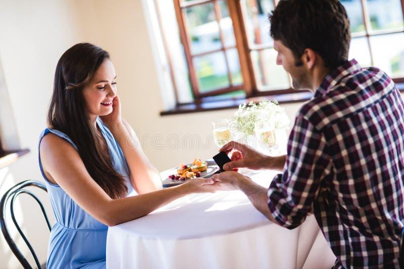 Man som föreslår till kvinnan i en restaurang royaltyfria bilder