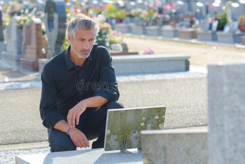Man som förlägger blommor vid gravstenen i kyrkogård fotografering för bildbyråer