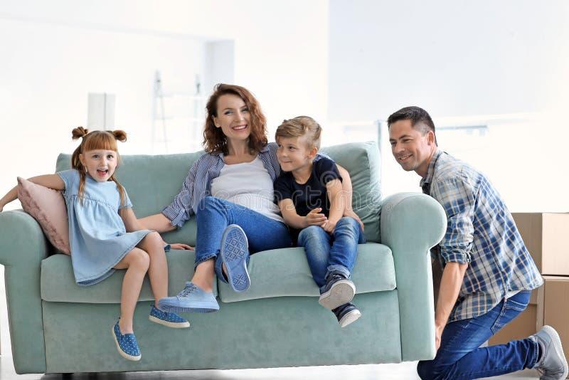 Man som försöker att flytta soffan med hans familj på det nya hemmet arkivbilder