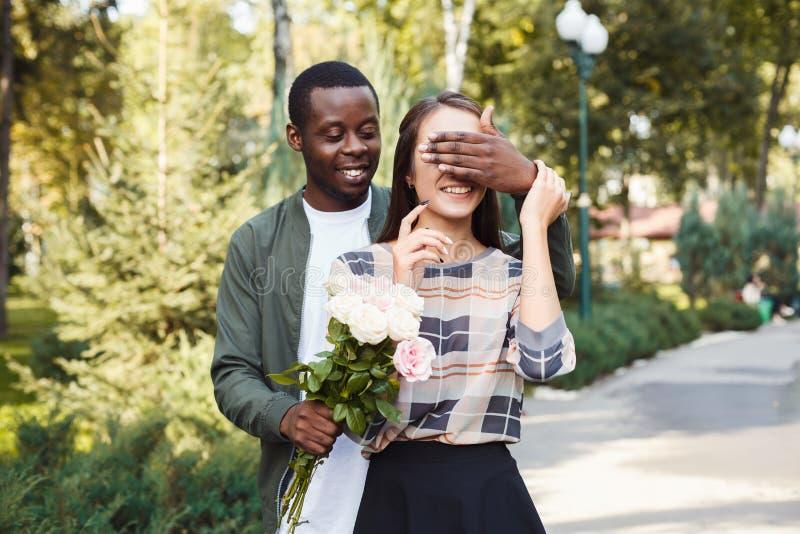 Man som förvånar hans flickvän med blommor arkivbild