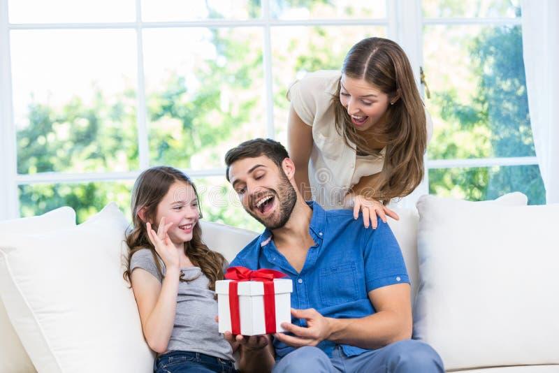 Man som förvånas med gåvan som ges av familjen royaltyfria bilder