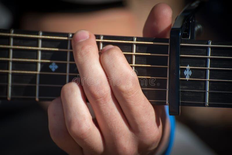 Man som fingrar ett ackord på en gitarr royaltyfri bild