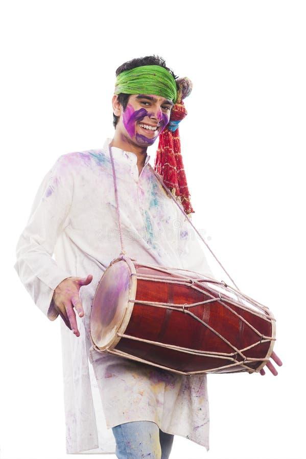 Man som firar Holi och spelar dholak royaltyfria foton
