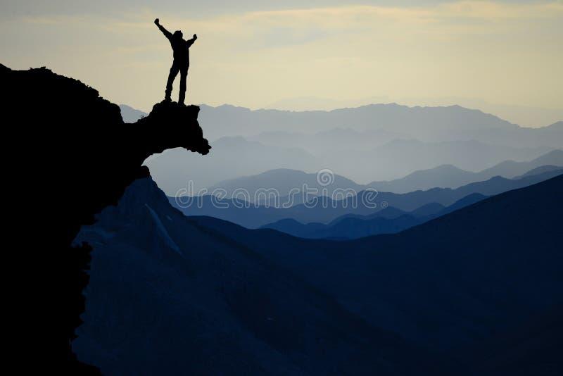 Man som firar på bergavsatsen royaltyfri fotografi
