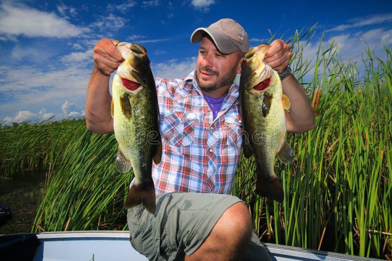 Man som fiskar den Largemouth basen arkivfoton