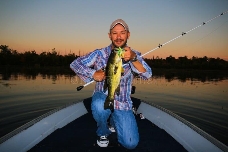 Man som fiskar den stora munnen Bass Sunset royaltyfria bilder