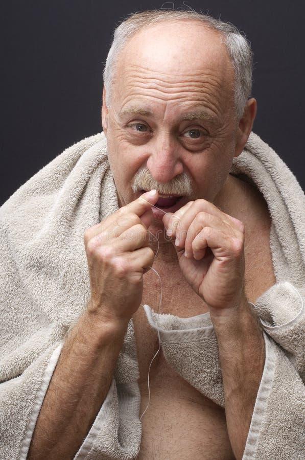 Man som Flossing hans tänder arkivfoton