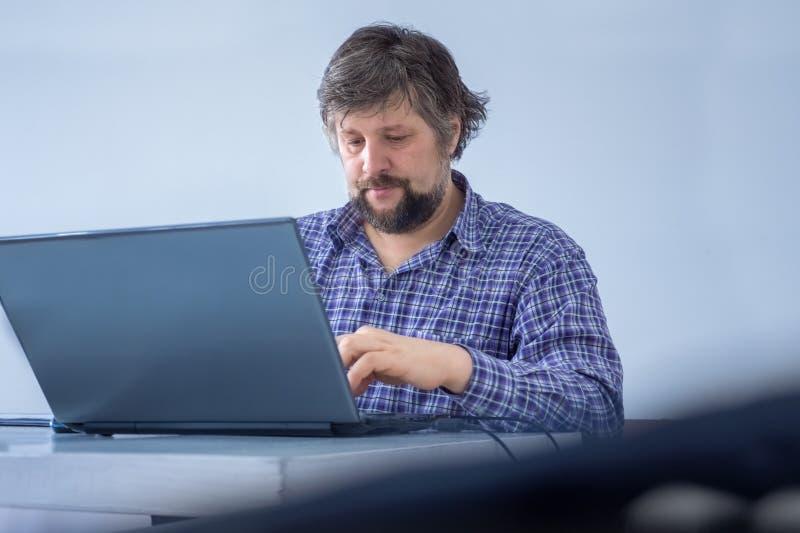 Man som fokuseras på arbete home working Den idérika massmediamarknadschefen som gör importnant uppgifter, har upptaget arbete arkivbild