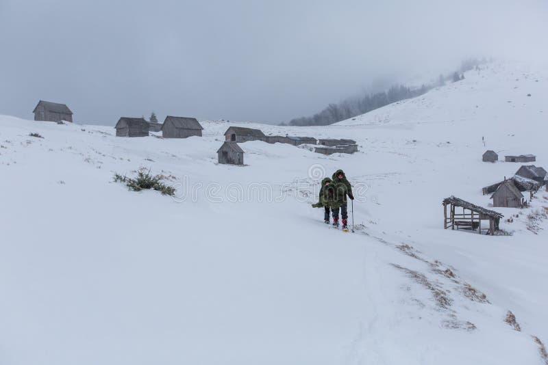 Man som fotvandrar i vinterberg för åskväder fotografering för bildbyråer