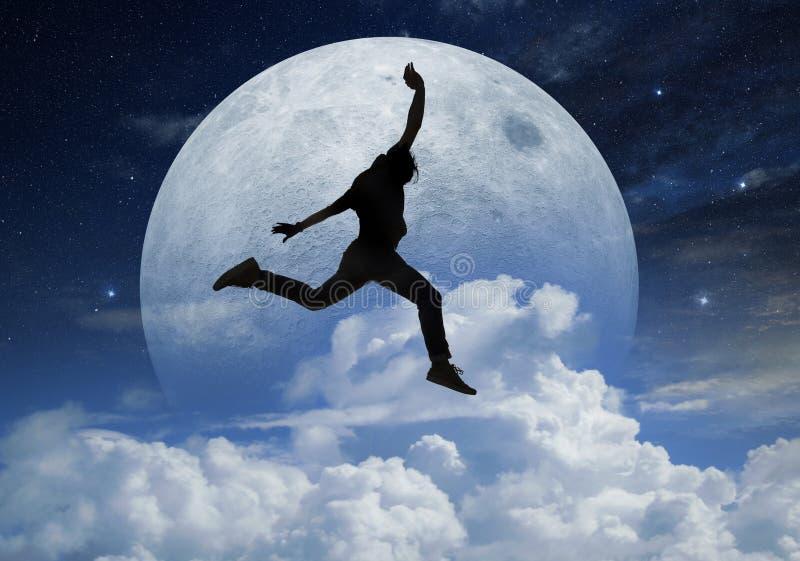 Man som framme hoppar en fullmåne royaltyfria foton