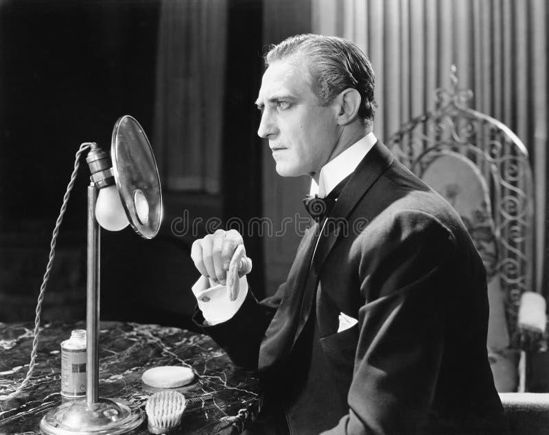 Man som framme sätter pulver på hans framsida av en spegel (alla visade personer inte är längre uppehälle, och inget gods finns l royaltyfria bilder