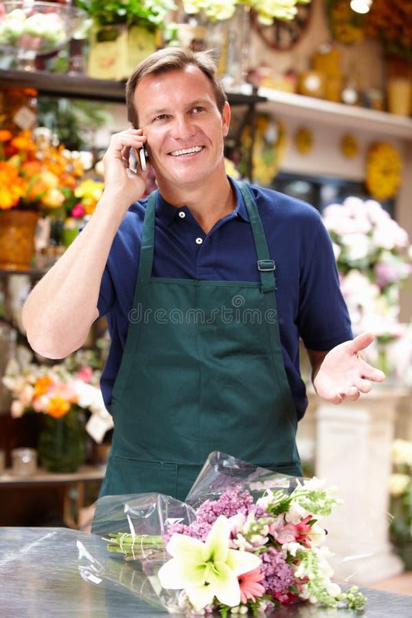 Man som fungerar i blomsterhandlare arkivbild