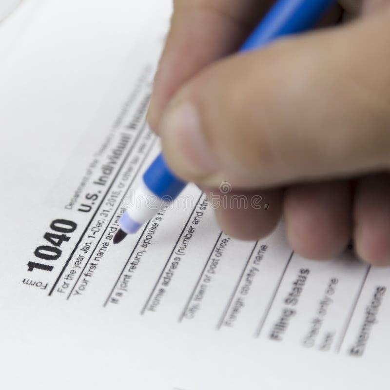 Man som fyller USA-skattformen skattform oss begrepp för påfyllning för hand för kontor för affärsinkomst arkivbilder