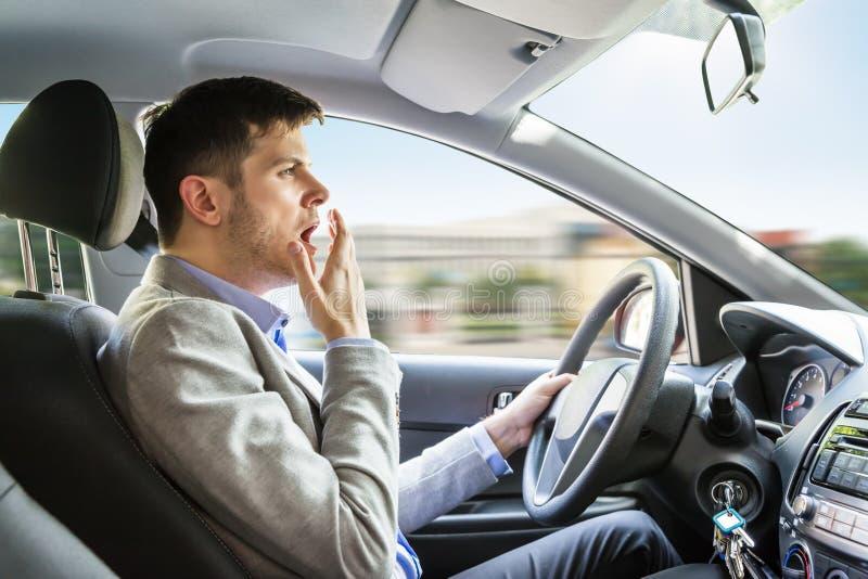 Man som gäspar, medan köra bilen arkivfoto