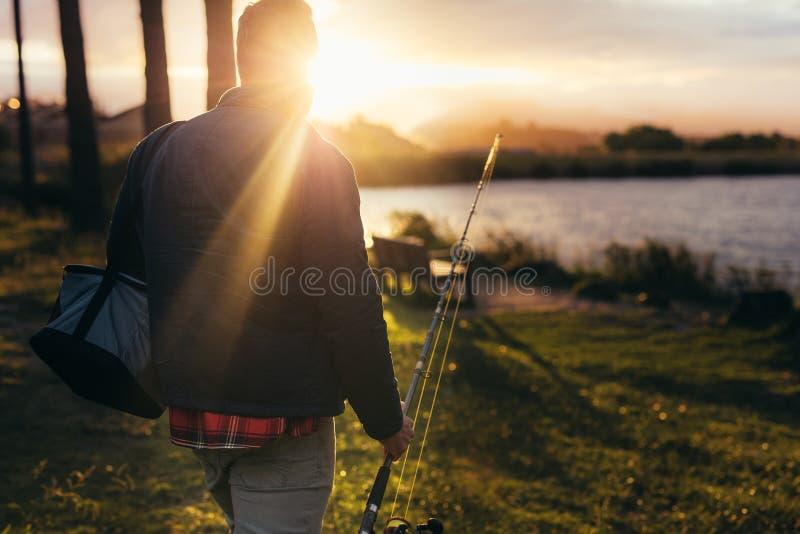 Man som går för att fiska nära en sjö royaltyfri fotografi