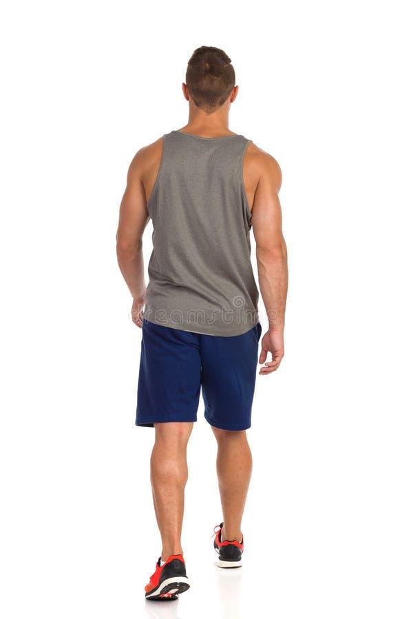 Man som går i sportkläder isolated rear view white isolerat royaltyfri fotografi