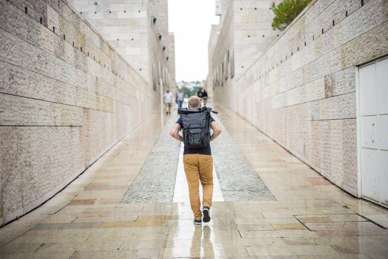 Man som går med ryggsäcken med tripoden under regnigt väder fotografering för bildbyråer