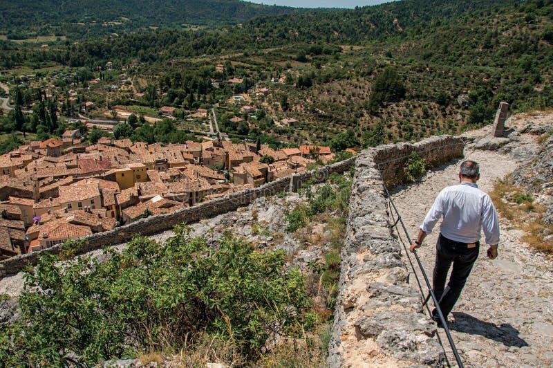 Man som går ner stentrappuppgång med tak av den Moustiers-Sainte-Marie byn under fotografering för bildbyråer