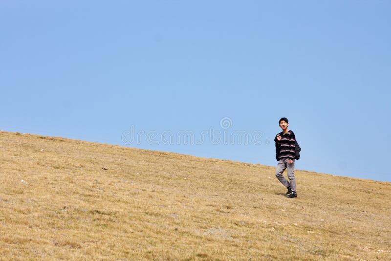 Man som går på berg arkivbild