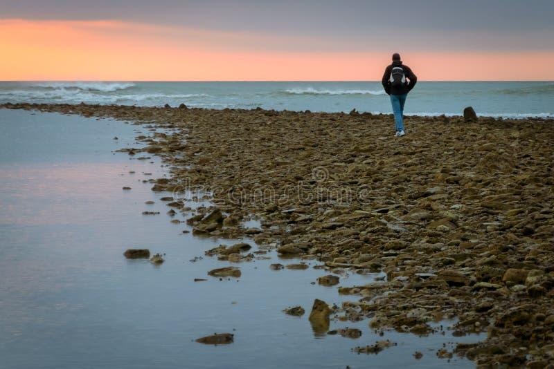 Man som går på stenarna av en strand på ön av beträffande france royaltyfri fotografi