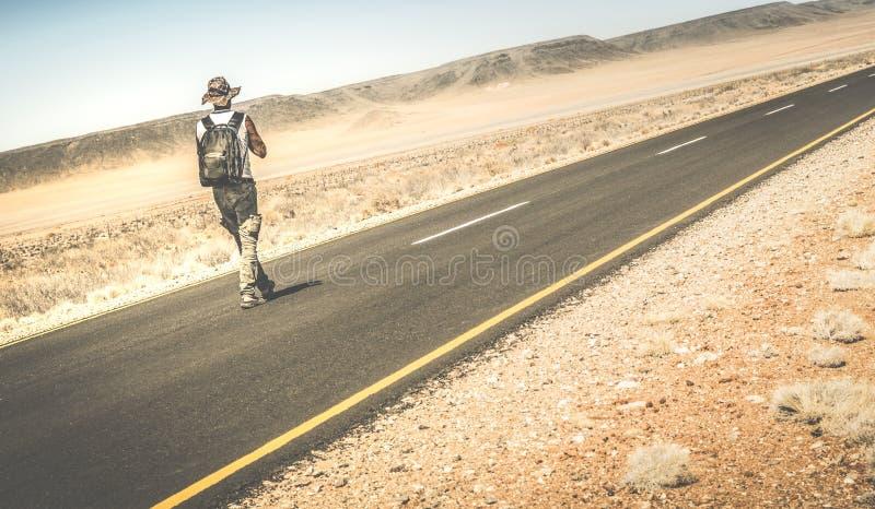 Man som går på vägen på namibian afrikansk öken arkivfoto